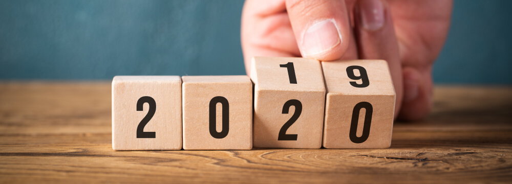 Four wooden blocks displaying the number 2019. A hand is turning the last two blocks so they say 2020 instead.