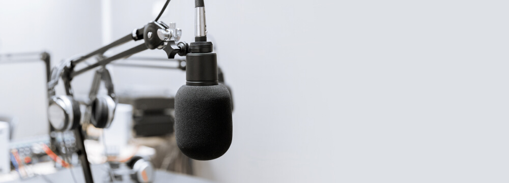 Image depicting recording studio room, with audio equipment in the background and a professional microphone on a stand in the foreground.