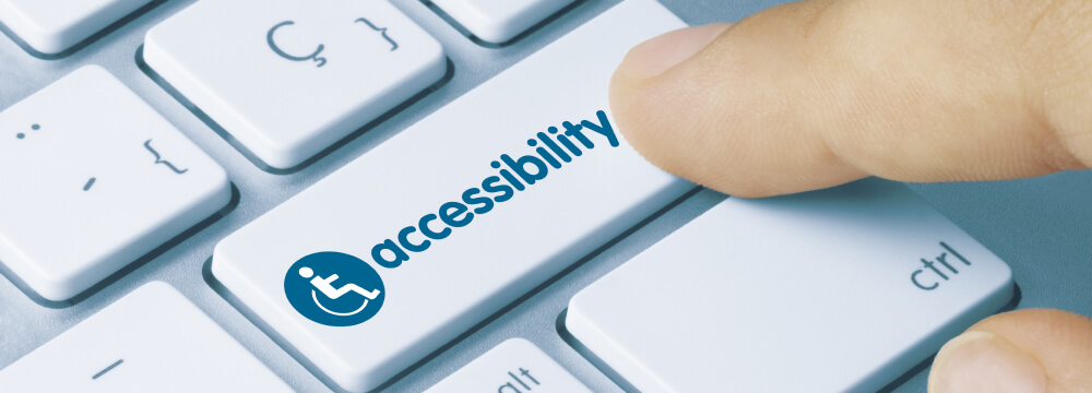 Finger pressing key on a computer keyboard saying 'accessibility'.