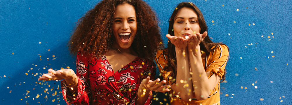 Two women celebrating by throwing and blowing gold confetti.