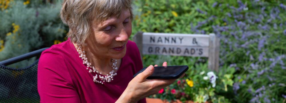 Elderly woman using her Pocket phone outside.